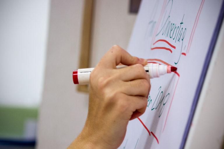 Hand schreibt auf Flipchart